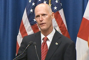 Gov. Rick Scott speaking with American flag in background